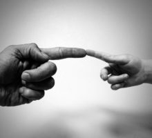 Adult hand and child hand pointer fingers touching